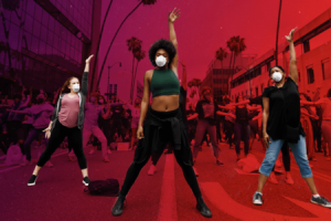 Hundreds of people are in the street. Three people in the front of the crowd are in the middle of a dance move, fists raised in the air.